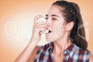 Composite image of woman having asthma using the asthma inhaler