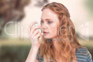 Composite image of beautiful woman using the asthma inhaler