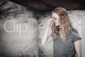 Composite image of blonde woman with headache pinching her nose