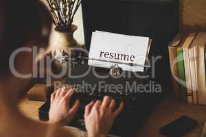 Resume against young woman using typewriter