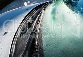 Frozen car windshield and wipers and hood.