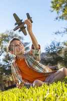 Young Boy Playing WIth Toy Model Airplane Outside