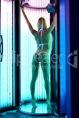 Rear view of slender blonde tans in tanning booth