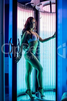 Pretty woman posing while tans in modern solarium