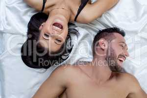 Top view of loving couple laughing in bed