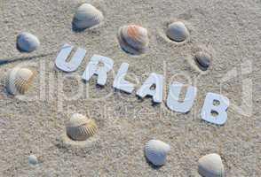 Urlaub Strand Buchstabend im Sand