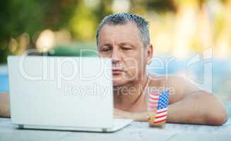 Man in Swimming Pool with Laptop and Beverage