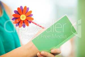 Woman Writing in Notebook with Flower Pencil