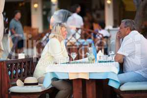 Middle-aged couple enjoying a meal and wine