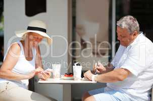 Couple sitting in cafe while using gadgets