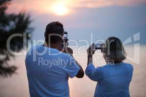 Back view of couple taking photos of sunset