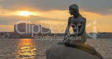 Mermaid statue on the stone in sea at sunset