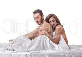 Erotica. Loving couple in bed, isolated on white