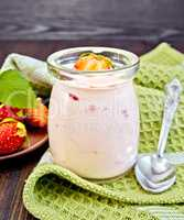 Yogurt with strawberries in jar on napkin
