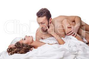Erotica. Man passionately hugging woman in bed