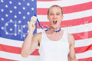 Athlete showing his gold medal in front of american flag