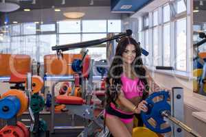 Nice brunette posing before training with barbell