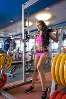 At fitness center. Nice girl training with barbell