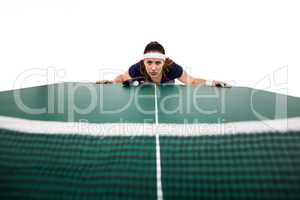 Confident female athlete leaning on hard table