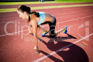 Confident female athlete in ready to run position