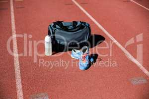 Sports bag, shoes and a water bottle kept on a running track
