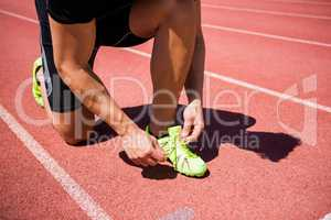 Male athlete tying his shoe laces on running track