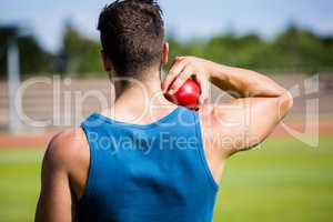 Male athlete about to throw shot put ball