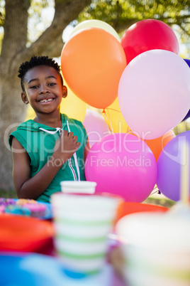 Cute boy smiling and posing next to balloon during a birthday pa