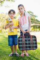Portrait of cute brother and sister posing with old luggage and
