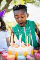 Portrait of cute boy preparing to blow on candle during a birthd