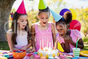 Portrait of cute girls preparing to blow on candle during a birt