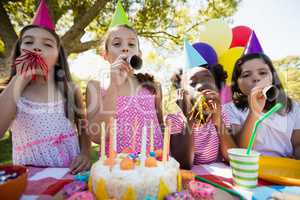 Children breathing out in a birthday trumpets during a birthday