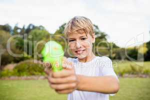 Kid posing at camera during a sunny day with his water gun