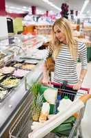 Blonde woman looking at prepared meal buffet