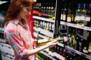 Side view of pretty woman choosing carefully a bottle of wine