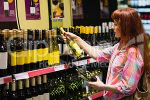 Consumer hesitating between two bottles of wine