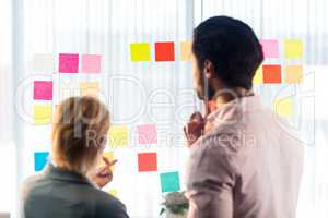 Rear view of two business people looking at post it wall