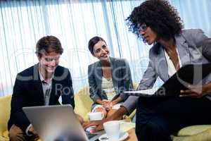 Coworkers having meeting around table