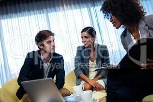 Coworkers having meeting around table