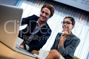 Low angle view of business associate looking a laptop