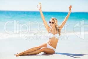 Woman posing with sun cream on beach