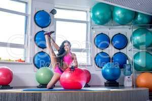 Beautiful sporty woman trains in modern gym