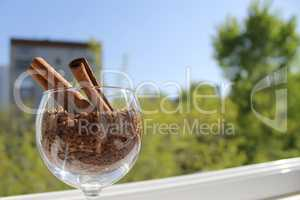 cinnamon sticks in a glass of wine with granulated coffee, daylight