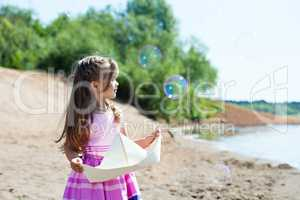 Nice little girl playing with paper boat