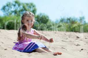 Cute curly-haired girl plays with sand