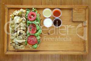 Open face healthy meat and vegetable sandwich served with condim