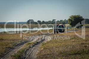 Jeep passengers on sandy track watching river