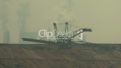 Open-cast mining. Defocus on excavator and power plant in the background. Surface mine.