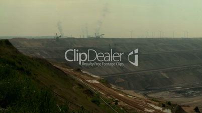 Open-cast mining. Establishing shot, pan from power plant to giant bucket-wheel excavator. Surface mine.