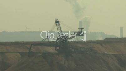 Open-cast mining. Defocus on filling up excavator. Power plant and wind engine in the background. Surface mine.